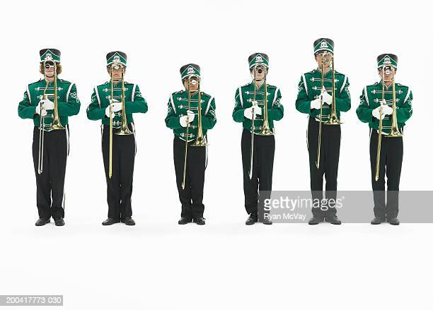 Six teenagers (15-17) in marching band uniforms holding trombones