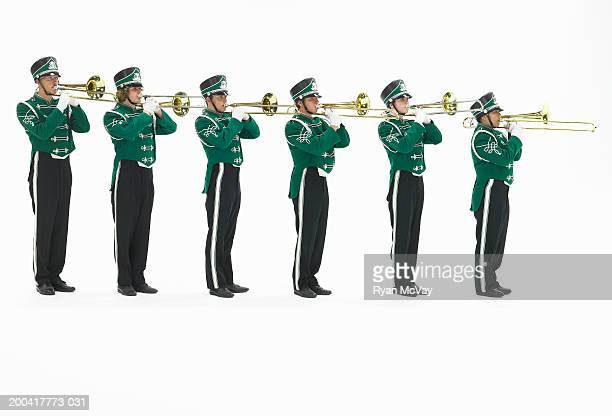 Six teenagers (15-17) in marching band uniforms playing trombones