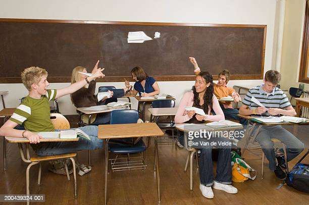 Six teenagers (16-18) throwing paper airplanes in classroom
