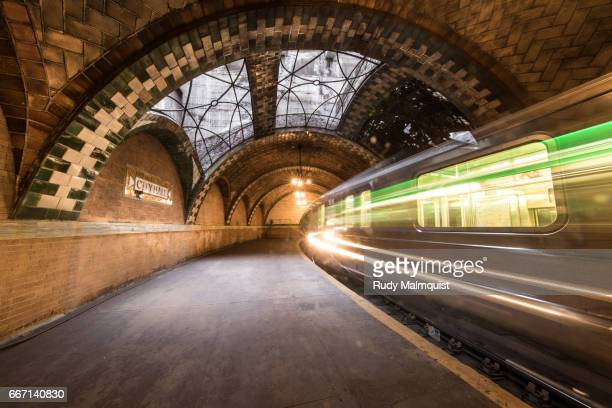 six train blurring through the abandoned city hall station in nyc - station stock-fotos und bilder