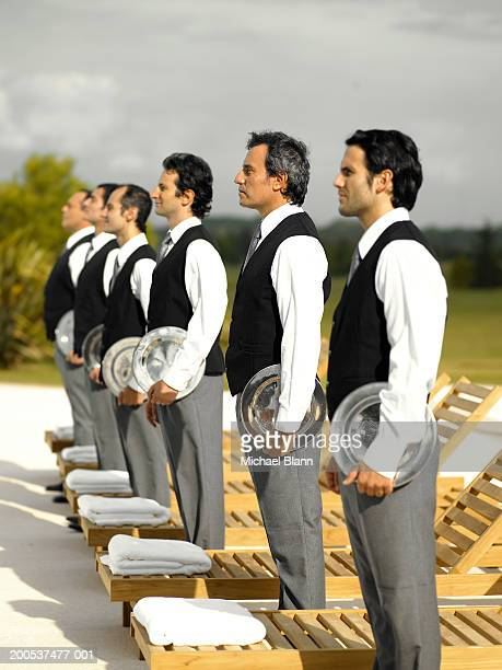 Six waiters holding trays standing by sunbeds on terrace