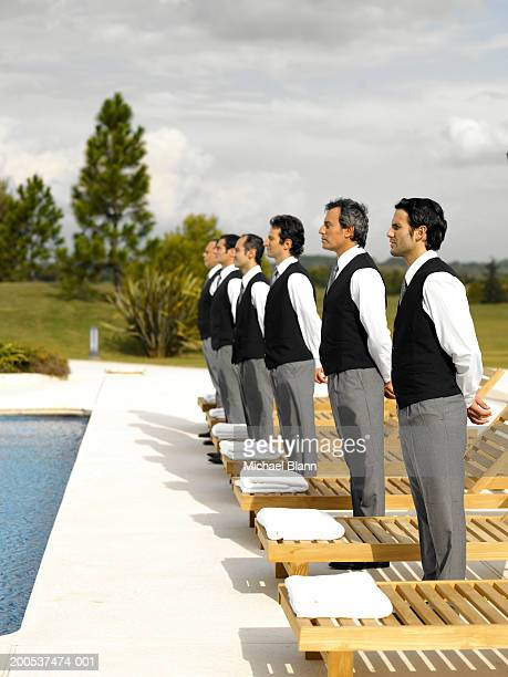 Six waiters standing to attention by sunbeds on pool terrace