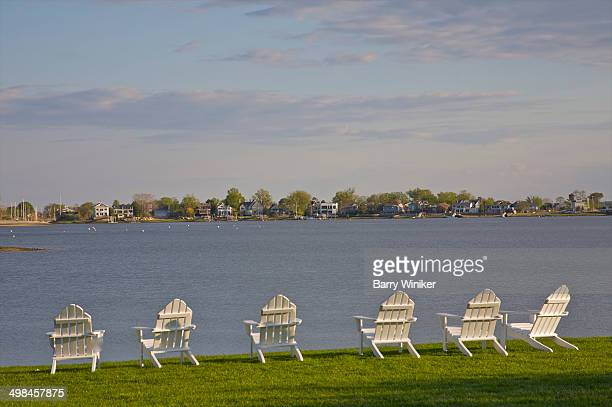 Six white chairs facing water and shoreline houses