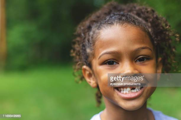 six year old african american chinese ethnicity girl posing for portrait in lush green outdoor back yard setting - children only stock pictures, royalty-free photos & images