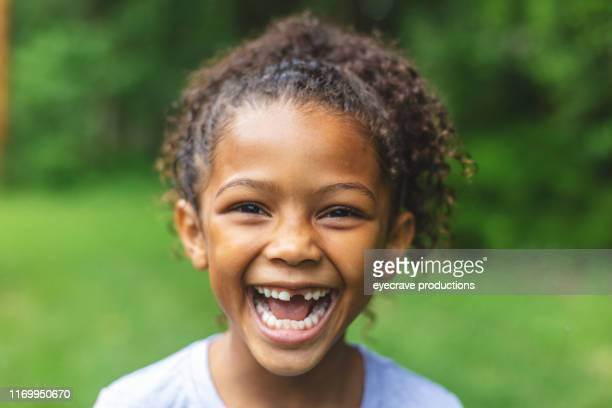 Six year old African American Chinese Ethnicity girl posing for portrait in lush green outdoor back yard setting