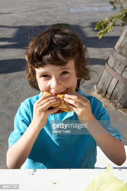 six year old boy eating hamburger - jason todd stock photos and pictures
