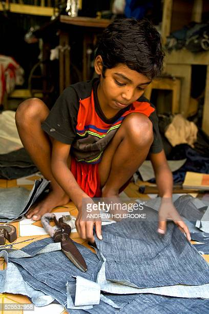 A six year old child laborer working in a small garment factory cuts cloth while the owner looks on Child labor is illegal in Bangladesh but...