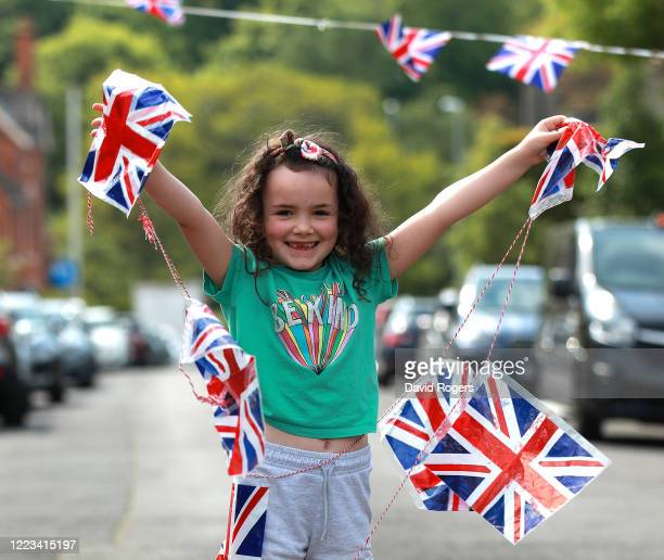 Six year old Ellie Ingham holds the string of flag bunting on May 07 2020 in Northampton United Kingdom The UK will commemorate the 75th Anniversary...