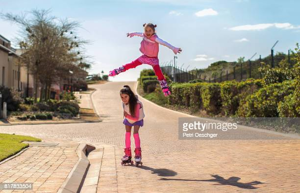Six year old girl leapfrogs her 10 year old sister on rollerblades.