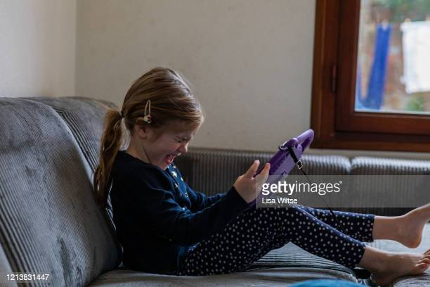 a six year old girl playing on her ipad. - lisa strain stock pictures, royalty-free photos & images