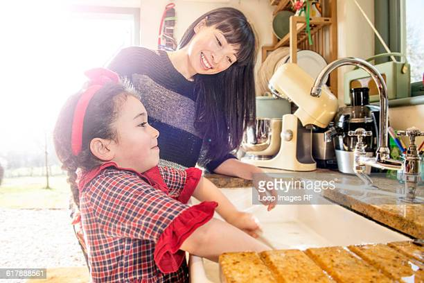 A six year old girl with her mother washing dishes in a kitchen sink