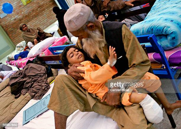Six year old injured earthquake survivor Hamida lies in the arms of an elderly man one hour after the amputation of her right leg in the Pakistan...