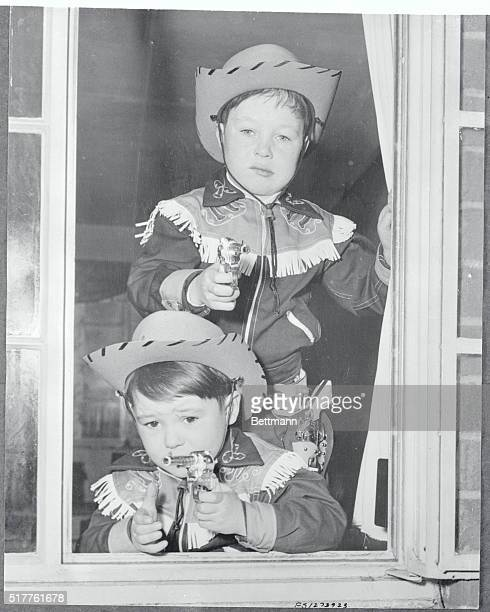 Six year old Michael Burke and his five year old brother Danny aim their weapons at photographers as they play cowboy in the new Texas cowboy suits...