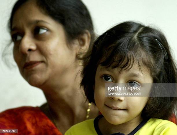 Six year old Pakistani child Fatima Khan smiles as she poses for photographers with her mother Farhana Naseem on a ward in a private hospital in...