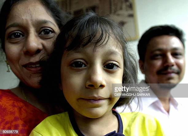 Six year old Pakistani child Fatima Khan smiles as she poses for photographers with her mother Farhana Naseem and father Naseem Ahmed Khan on a ward...