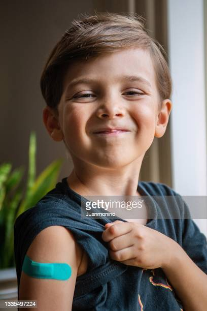 six years old child showing his band aid just after being vaccinated - 6 7 years stock pictures, royalty-free photos & images