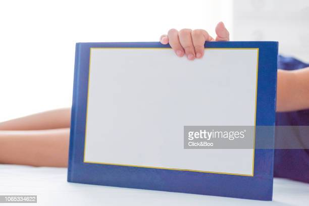 Six years old kid holding a book on a bed (home interior)