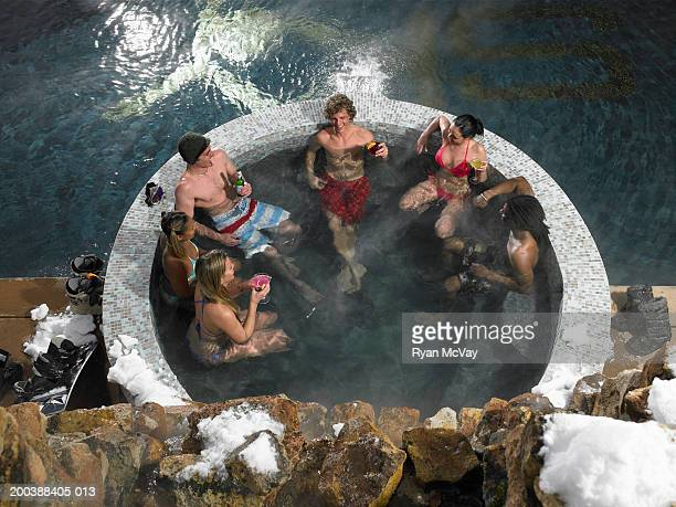 Six young adults drinking alcohol in hot tub, winter, elevated view