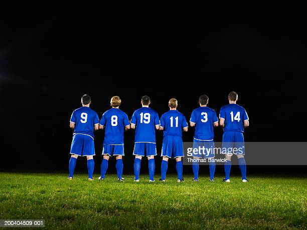 Six young male soccer players standing side by side, rear view