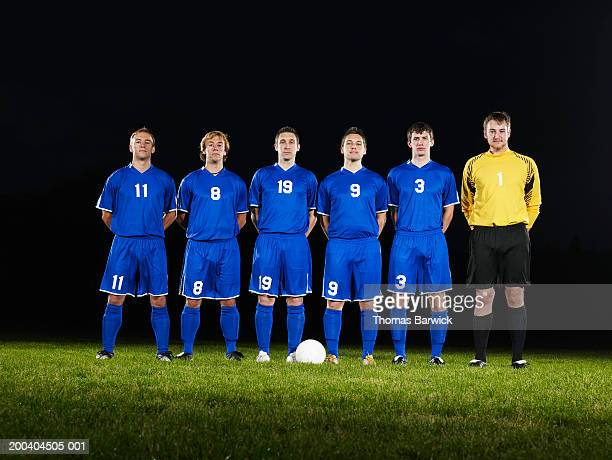 Six young male soccer players with hands behind backs, portrait