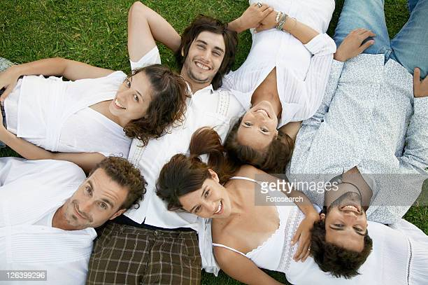 Six young people lying on grass (portrait, directly above)