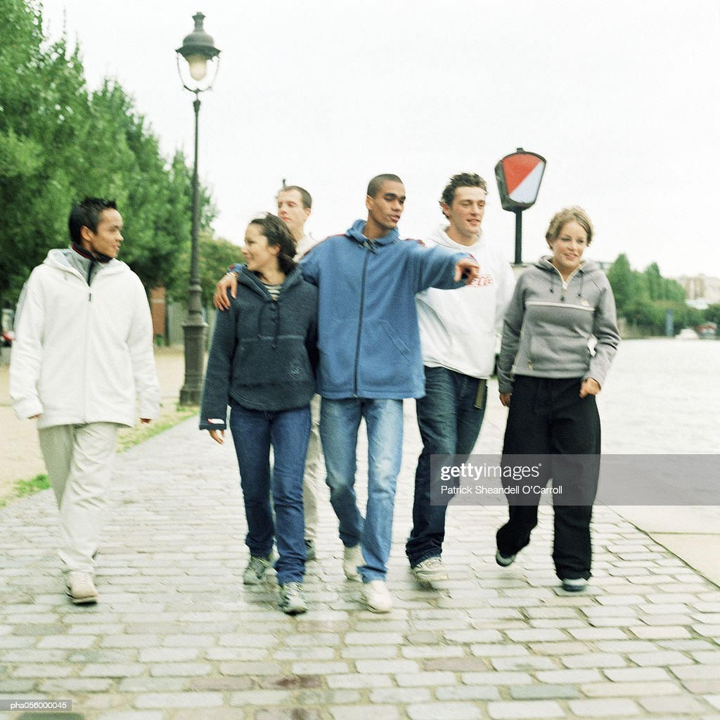 Six young people walking together on cobblestones : Stockfoto