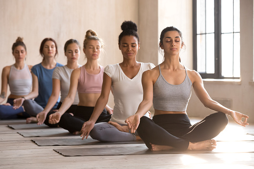 Six young women meditate sitting in lotus posture 1092303536