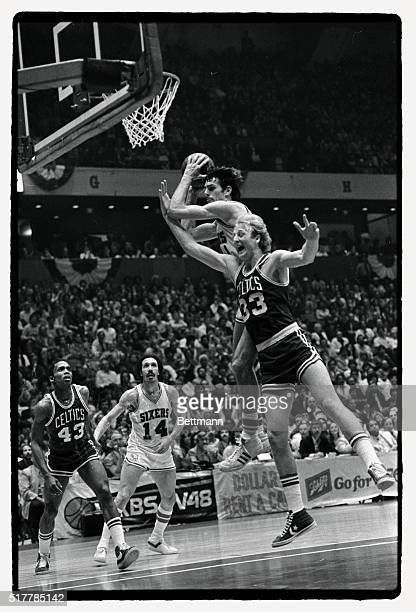 Sixers' Bobby Jones takes a rebound away from the outstretched arms of Boston's Larry Bird during the first quarter of an NBA semifinal game 4/23...