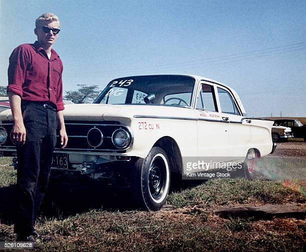 Sixteen year old boy stands with his 1960 Mercury Comet automobile ca 1962