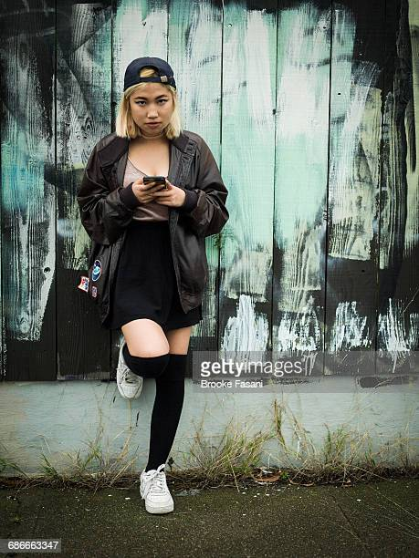 sixteen year old chinese teen with cellphone - teenagers only stock pictures, royalty-free photos & images