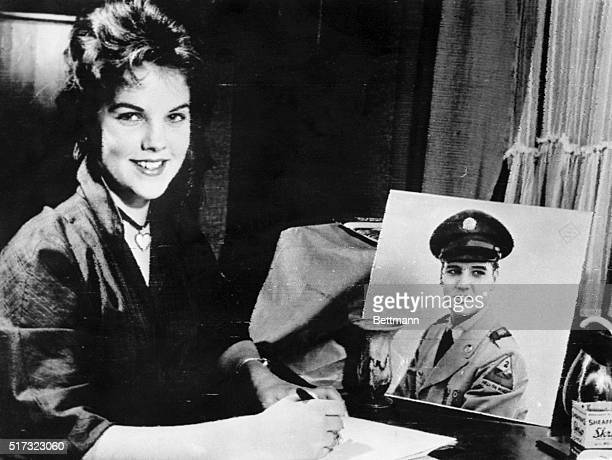 Sixteen year old Priscilla Beaulieu sits before a portrait of a uniformed Elvis Presley as she writes the singer and film star a letter. Beaulieu,...