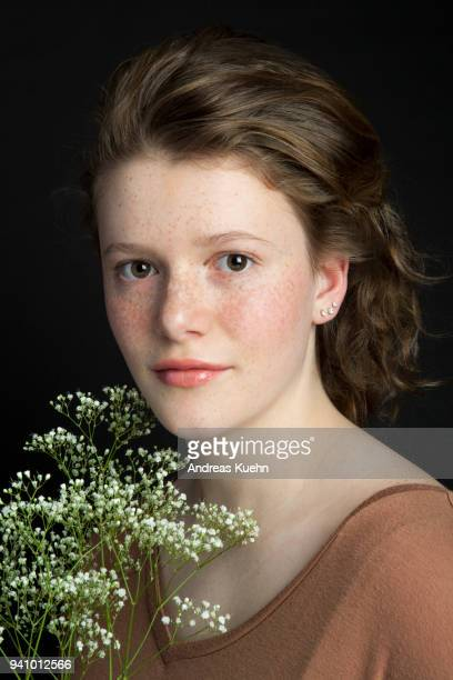 Sixteen year old teenage girl in front of a black background with a soft smile, pale complextion and freckles holding some white wildflowers, portrait.
