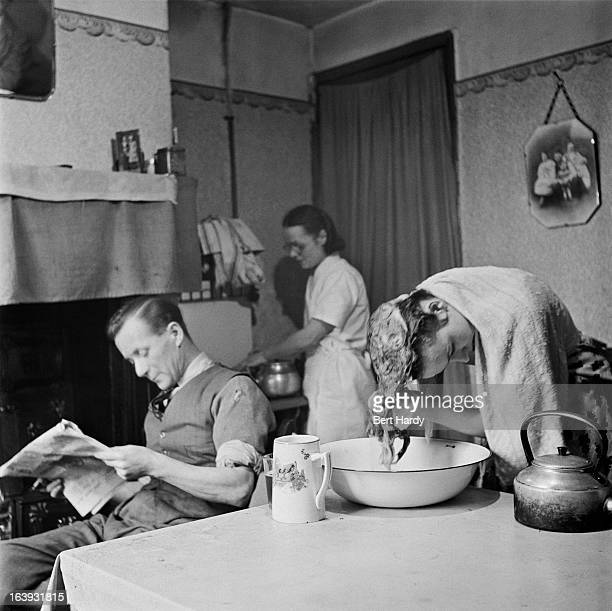 Sixteen yearold hairdresser Betty Burden washing her hair at her home in Back Chapel Court Birmingham January 1951 Her father is reading the 'News Of...