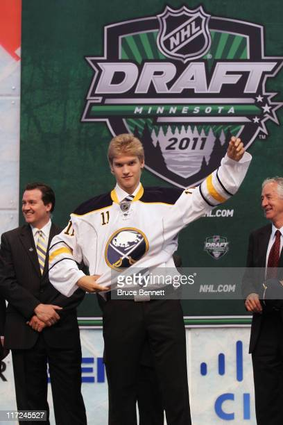 Sixteenth overall pick Joel Armia by the Buffalo Sabres stands onstage and puts on a Buffalo Sabres jersey during day one of the 2011 NHL Entry Draft...