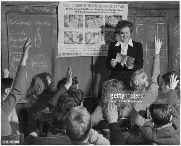 A sixth grade teacher shows her pupils on how to use War Ration Book Two February 1943