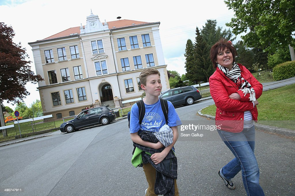 Sixth grader Benno Bluhm leaves with his mom after school at the Middle School on May 14, 2014 in Seifhennersdorf, Germany. The state of Saxony officially closed the Seifhennersdorf Middle School in 2012 after only 38 students registered, two short of the 40 the state required to keep the school open. Rather than agree to the school's closing, a group of parents and other volunteers have since assumed the duties of teachers and staff themselves and are trying to get recognition of their 'illegal' school through a court case that now lies with Germany's Federal Constitutional Court. Eleven 6th graders attend the school, even though the state does not recognize their enrollment. School closings across Germany have reached epidemic proportions with 6,100 closures between 2003 and 2013, due in large part to Germany's low birth rate, a phenomenon typical across much of Europe. In Saxony the low birth rate has combined with a steady migration of young people to big cities and to western Germany and the number of schoolchildren has fallen by close to 50% and led to the closure of 1,000 out of a total of 2,500 state schools since 1989.