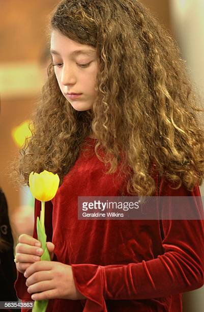 Sixth grader Sophie Miller holds one of seven yellow tulips during a program to remember 6 million Jews who perished in the Holocaust and 1 million...