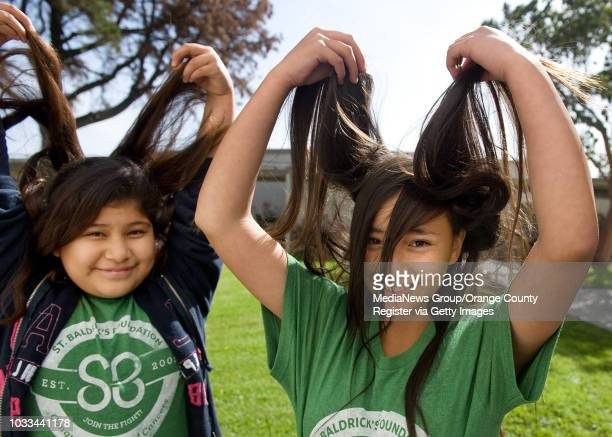 Sixth graders Esther Calderon at left and Rosalba Cabrera show off their long locks of dark brown hair before it is shaved off at Carr Intermediate...