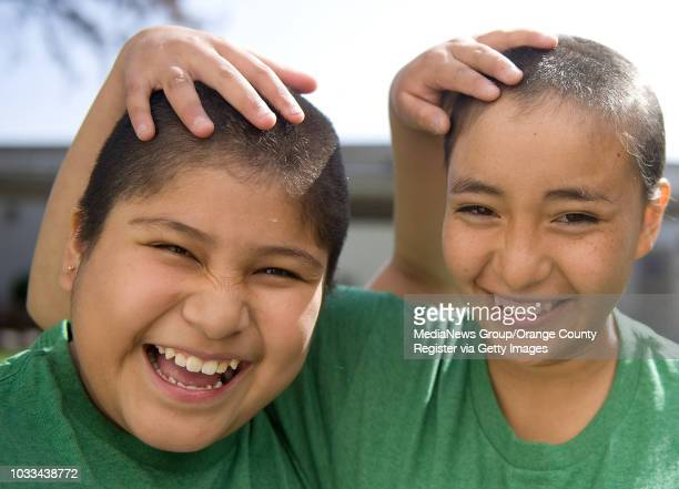 Sixthgraders Esther Calderon at left and Rosalba Cabrera adjust to theirfreshly shaved heads after getting more than a foot of hair shaved off at...