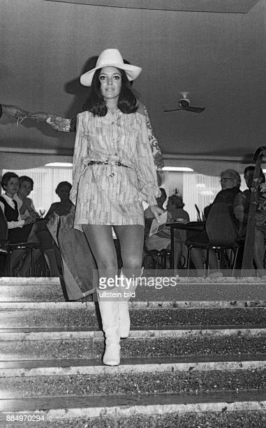 Sixties black and white photo people fashionshow young woman 20 to 25 years on a staircase longhaired minidress hat high boots