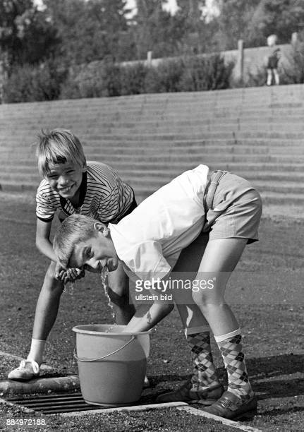 Sixties black and white photo people summer heat two boys 10 to 13 years refreshing at a water bucket short trousers kneelength socks