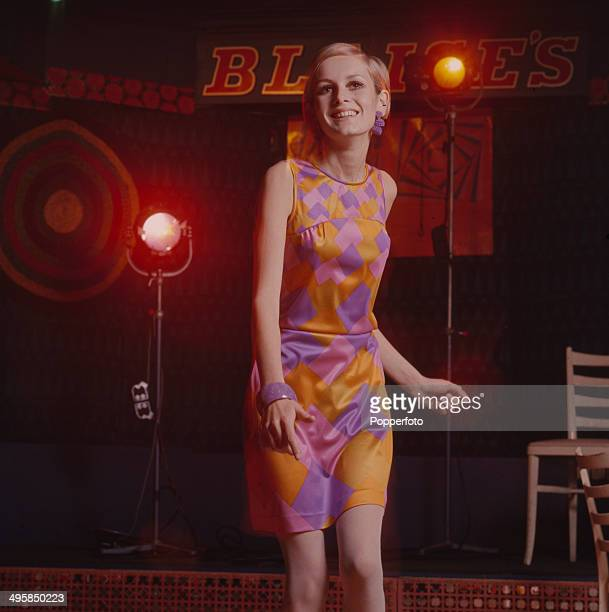 Sixties Fashion A portrait of model Twiggy wearing a purple and gold diamond print dress whilst dancing at Blaises Nightclub in Kensington London in...
