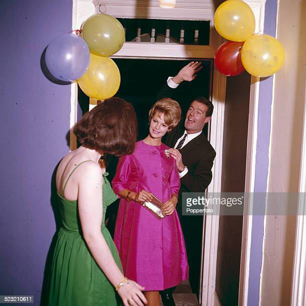 Sixties Fashion A young couple arrive at a house party her dressed in a pink knee length swing coat and him in a suit to be greeted by the female...