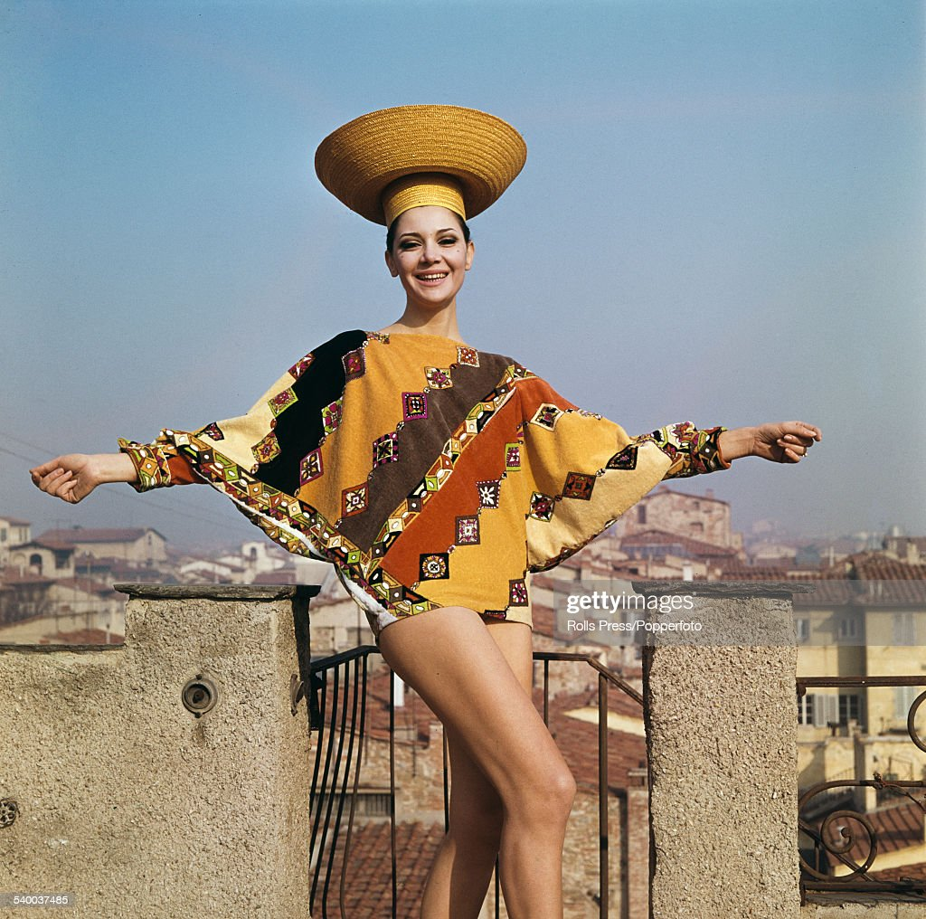 Sixties Fashion - A young female model wears a beach outfit in shades of orange, yellow and brown in a diagonal pattern, the hip hugging tunic having batwing sleeves over a blouse with sleeves ending in spur like cuffs and a straw basket hat, designed by Emilio Pucci for the fashion house's Spring/Summer collection in Florence in February 1964.