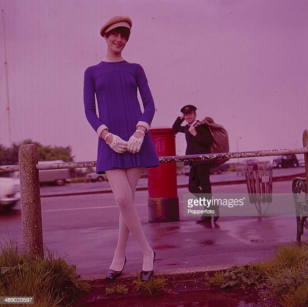 Sixties Fashion A young female model wears a blue mini dress with white tights gloves and a cap A postman holding a sack of letters stands in the...