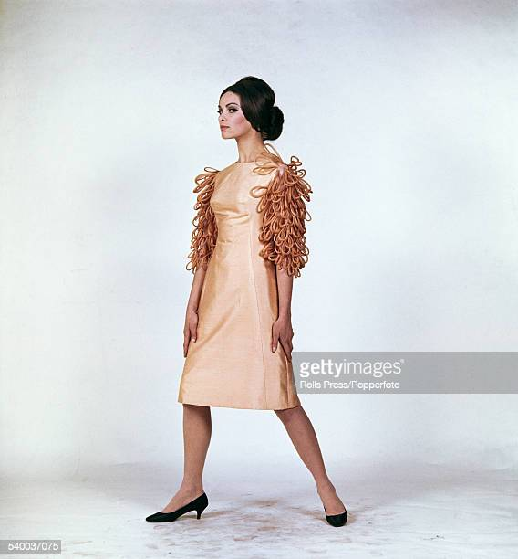Sixties Fashion A young female model wears a cocktail dress in smooth goldyellow pure silk with frilly capriccio carnival style sleeves of darker...