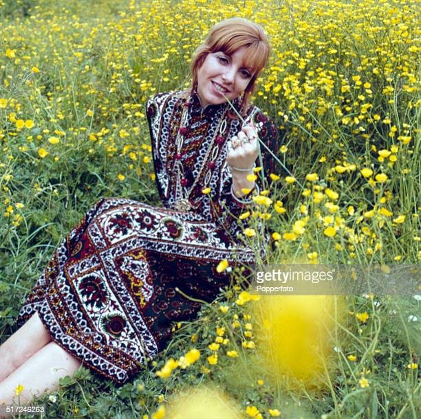 Sixties Fashion A young female model wears a Gipsy style dress in a field of buttercups circa 1968