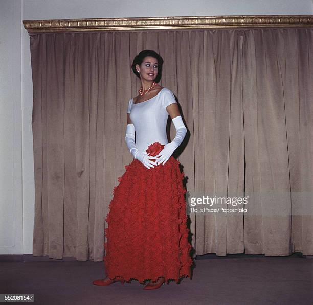 Sixties Fashion A young female model wears a grand soiree dress in white linen and lacered 'guipure' for the bodice and the gown respectively the...