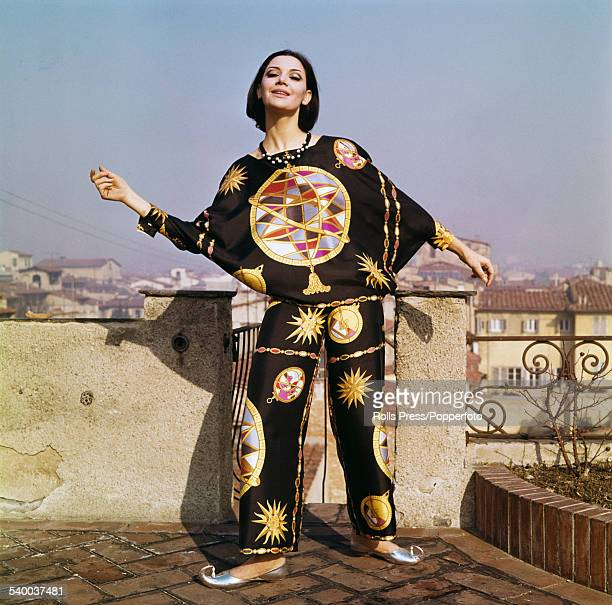 Sixties Fashion - A young female model wears a harem flavoured beach pajama in silk twill with zodiac emblems printed in gold and orange on a black...