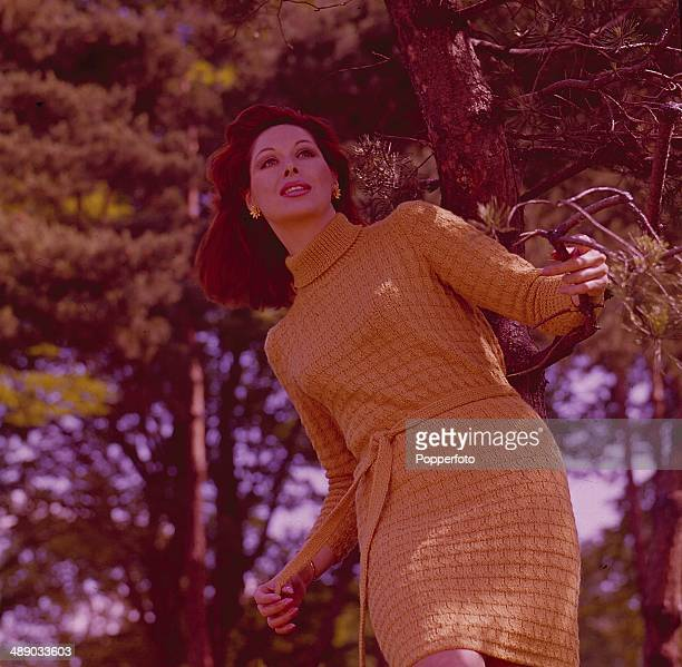 Sixties Fashion A young female model wears a knitted mustard coloured hostess dress in front of a backdrop of trees